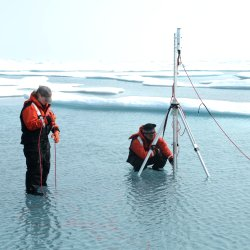 At work under the ice. The team of researchers is measuring the light transmittance below the ice in the Arctic.
